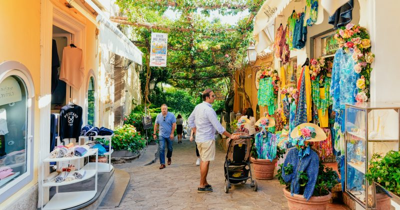 Positano, Italy - September 30, 2017: People doing shopping at street stores and market in Positano town of Amalfi Coast in Italy in summer. Tourists near Sorrento. Travel and tourism.