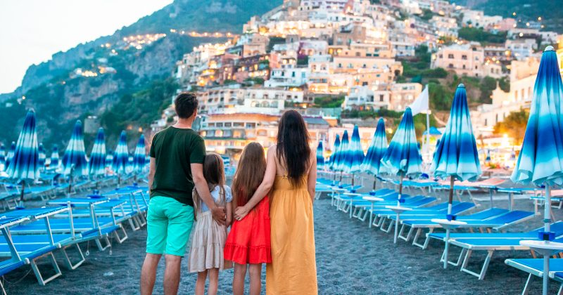 Family of parents and kids in front of Positano on the Amalfi coast in Italy in the evening
